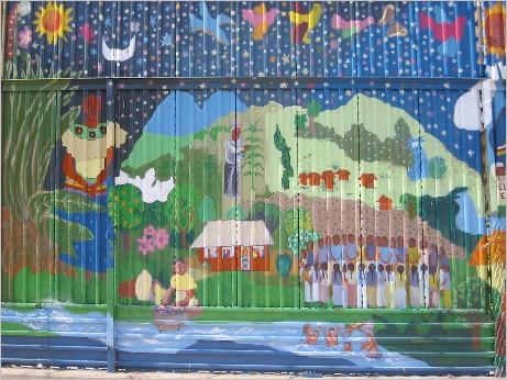 """Reproduction of """"Vida y sueños de la cañada Perla"""" [""""Life and Dreams of the Perla River Valley""""], Mexican side of the U.S. wall at the U.S.-Mexico Border, Nogales, Mexico. Originally painted in Taniperla, Chiapas by Sergio Valdéz Ruvalcaba and destroyed by paramilitary"""